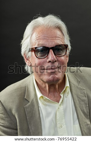 Studio portrait of senior man in suit with sunglasses looking tough and cool.