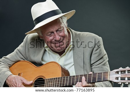Studio portrait of senior man with hat and guitar. Jazz musician.