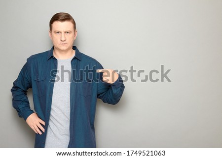 Studio portrait of serious blond mature man wearing casual blue shirt, pointing with index finger at himself, looking confident and strict, standing over gray background, copy space on right ストックフォト ©
