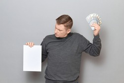 Studio portrait of serious mature man wearing casual jumper, holding bunch of US dollars and white blank paper sheet with place for your text or design, looking at paper, standing over gray background