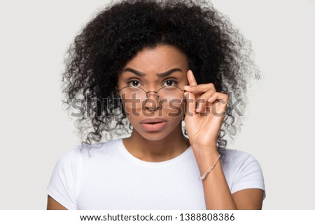 Studio portrait of shocked african young woman teacher wearing white t-shirt lowering glasses looking at camera feels confused surprised received amazing stunned news posing isolate on grey background