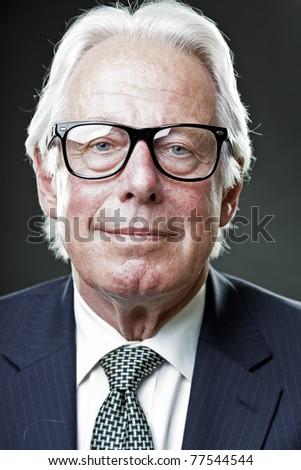Studio portrait of smiling senior man in suit wearing glasses.