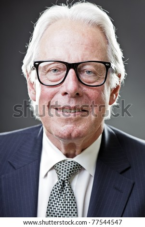 Studio portrait of smiling senior man in suit wearing glasses.