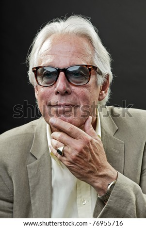 Studio portrait of smiling senior man in suit wearing sunglasses.