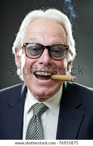 Studio portrait of smiling senior man in suit with big cigar wearing sunglasses.