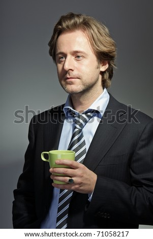 Studio portrait of smiling young business man holding cup of coffee. Relaxed. Having a break. Happy. Lucky.