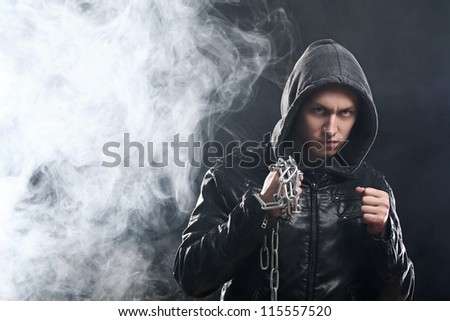 Studio portrait of street fighter with chains over his fist