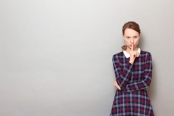 Studio portrait of strict girl wearing checkered dress, showing silence gesture with finger over lips, requiring to stop talking and keep mouth shut, standing over gray background, with copy space