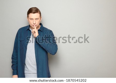 Studio portrait of strict mature man wearing casual shirt, showing silence gesture with finger over lips, requiring to stop talking and keep mouth shut, standing over gray background, with copy space ストックフォト ©