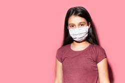 Studio portrait of teenage girl wearing medical face mask against coronavirus. Prevention of covid-19. Background of pastel pink color with copy space.