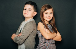 Studio portrait of two cute kids, standing back to back, arms crossed, posing on black background