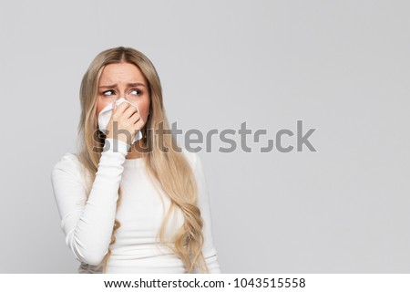 Studio portrait of unhealthy cute blonde female in white top with napkin blowing nose, looks to the source of the allergy, place for advertising/Rhinitis, cold, allergy concept/