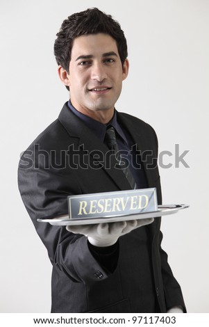 Studio portrait of waiter holding reserved sign