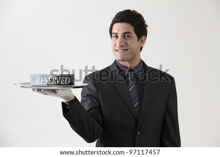 Studio portrait of waiter holding reserved sign