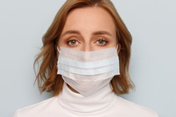 Studio portrait of woman wearing face medical mask, looking at camera, isolated on blue background, close up. Flu epidemic, dust allergy, protection against virus. Covid-19, coronavirus pandemic
