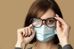 Studio portrait of woman with foggy glasses caused by wearing disposable mask. Protective measure during coronavirus pandemic. Medical mask and glasses fogging concept.