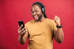 Studio portrait of young African American guy with dreadlocks in wireless headphones isolated on red wall saying yes, looking at mobile phone, enjoying listening to favorite music soundtrack, dancing
