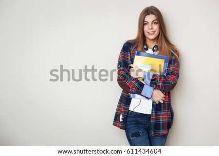 Shutterstock Studio portrait of young beautiful female student with books standing against wall.