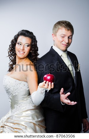 Studio portrait of young beautiful happy just married bride offering a red apple to doubting groom on gray background