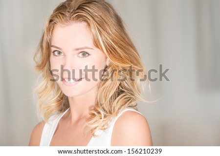 studio portrait of young beautiful woman looking at camera and smiling