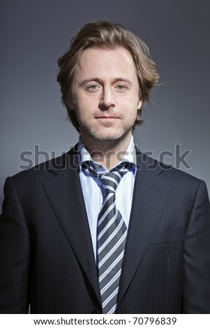 Studio portrait of young business man smiling. Suit and tie.