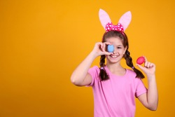 Studio portrait of young girl wearing traditional bunny ears headband for easter, covering her eyes with an egg and smiling. Brunette female with pigtails over yellow background. Close up, copy space.