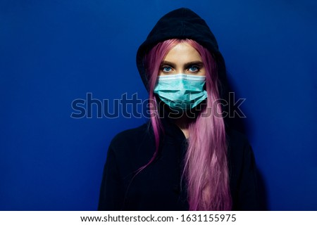 Photo of  Studio portrait of young girl with pink hair and blue eyes, wearing medical flu mask and hooded sweater on background of phantom blue color.