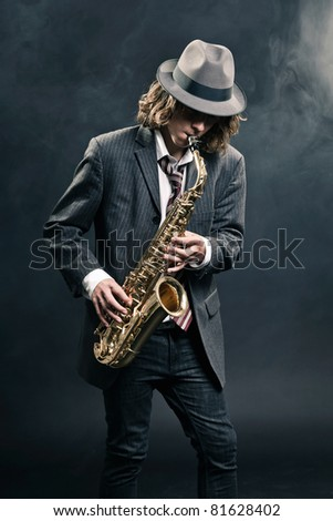 Studio portrait of young hip cool man with saxophone wearing hat and tie on black background. - stock photo
