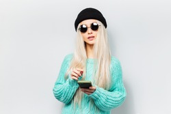 Studio portrait of young hipster blonde girl using smartphone on white background. Wearing round sunglasses and black beanie hat.