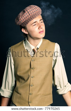 Studio portrait of young man in 20s style smoking cigarette wearing cap on black background.