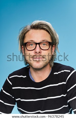 Studio portrait of young man with long blond hair wearing glasses and black sweater. Isolated on light blue background.