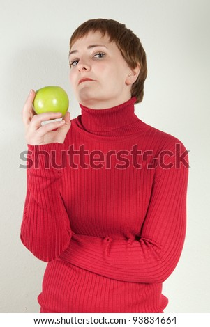 Studio portrait of young redhead woman holding green apple and looking wicked.