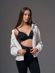 studio portrait of young slim tanned caucasian girl in black jeans, bra and white jeans jacket standing and posing against grey studio background