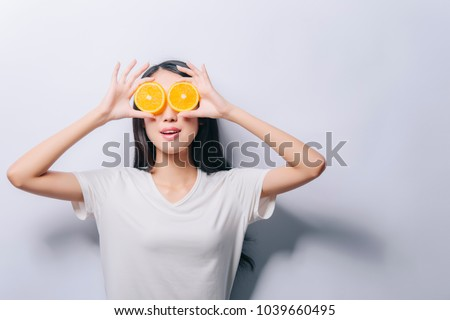 Studio portrait of young surprised happy asian girl holding two orange slices in t-shirt on white background and smiling. Fresh fruits and healthy diet concept. Free copy space provided