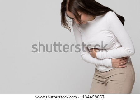 Studio portrait of young woman having a stomachache, menstruation pain or cramps, isolated on grey background.Chronic gastritis, period menstruation, female health problem, aching belly and gynecology