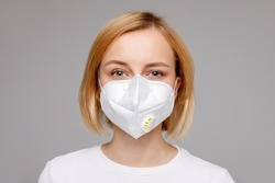 Studio portrait of young woman wearing a face mask, looking at camera, close up, isolated on gray background. Flu epidemic, dust allergy,  protection against virus. City air pollution concept