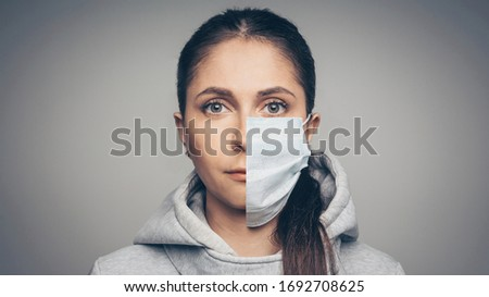 Photo of  Studio portrait of young woman wearing a face mask, looking at camera, close up on gray background. One half face in mask another without