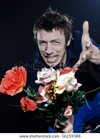 studio portrait on black background of a funny expressive caucasian man offering flowers ange