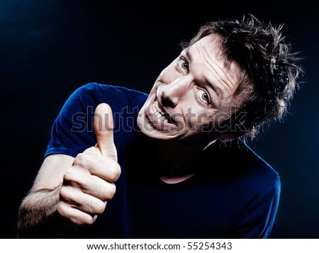 studio portrait on black background of a funny expressive caucasian man thumb up cheerful