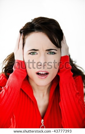 studio portrait on isolated background of a beautiful  caucasian expressive woman suffuring loud sound