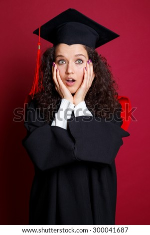 Studio portrait picture from a young graduation woman on red background #300041687