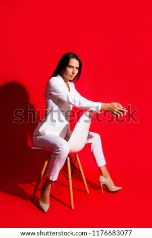 Stock Photo Studio posing snap photoshooting concept. Portrait of stunning cool woman sitting on chair looking at camera isolated on vivid red background