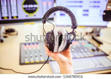 Studio recording: Young is holding headphones in the recording studio, studio in the blurry background #1368780416