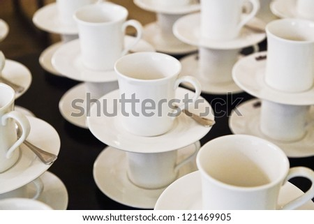 Studio setting of a hospitality serving beverages. Cups, saucers and teaspoons ready for service and interval drinks.