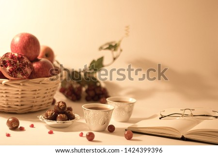 studio setup of elegant luxurious setup with an  open book, reading glasses, dates, arabian, persian tea cups a fruit basket with apples, pomegranate and grapes