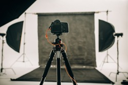 Studio setup with black background and studio flash lights with a DSLR camera on a tripod.