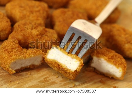 Studio shooting of a fried chicken pieces (nuggets) on wooden desk