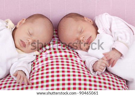 studio-shot a identical ( similar ) baby twin girls sleeping on a pillow. - stock photo