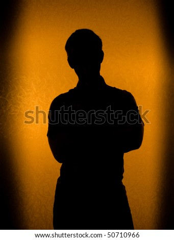 Studio shot - Back lit silhouette of man in the darkness