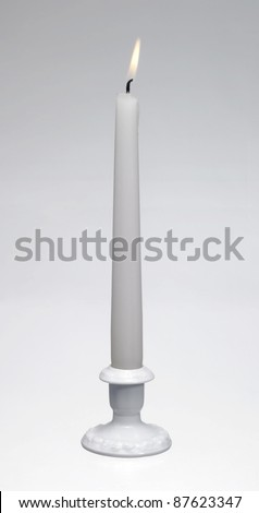 Studio shot of a a white burning candle and a white porcelain candle holder in light back